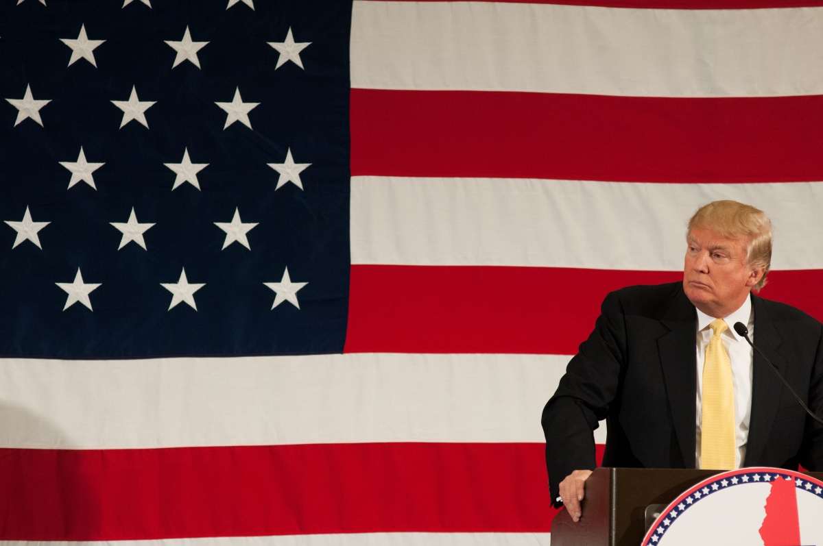 Donald Trump standing in front of a large American flag