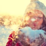 Young lady blowing snow from her hands towards the camera