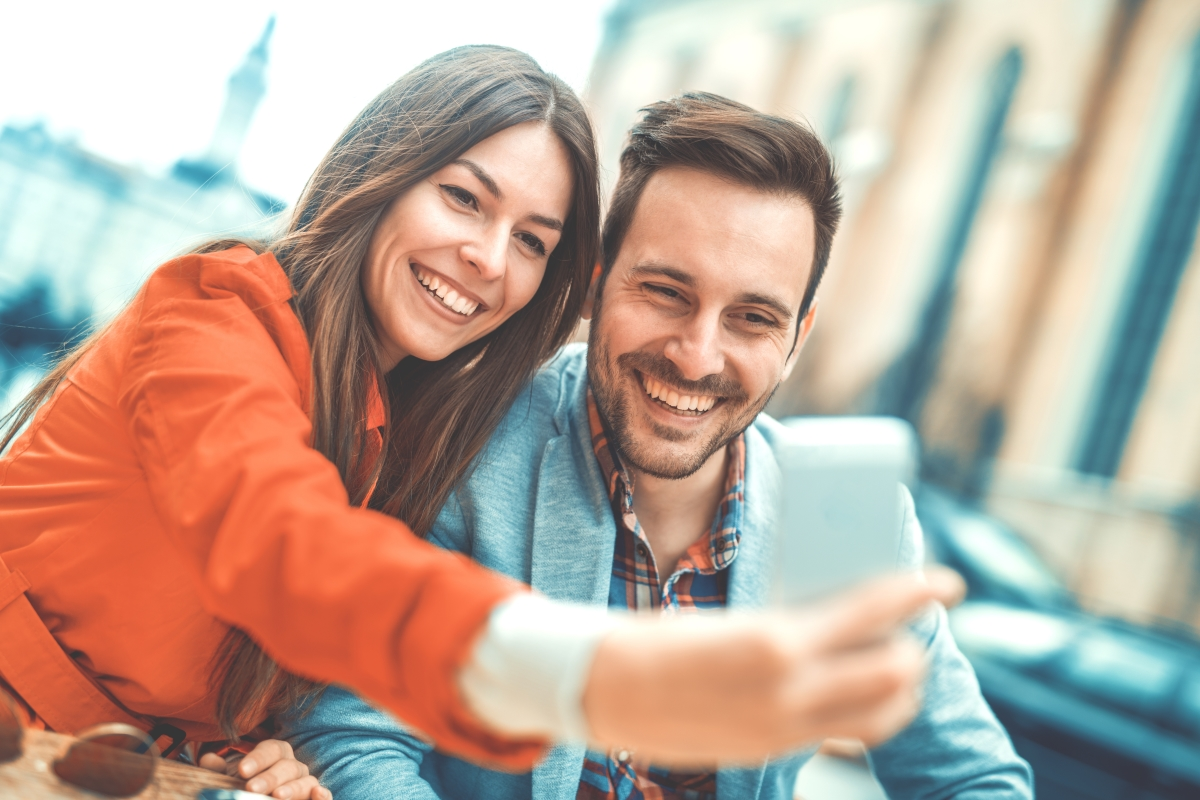 Man and woman taking a selfie with a smart phone